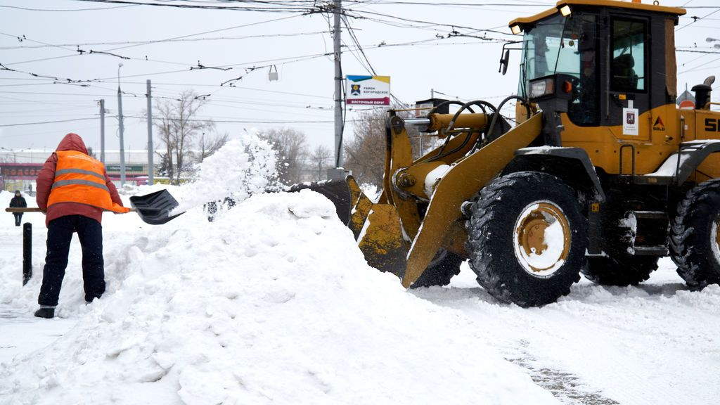 EuropaPress_3561702_13_february_2021_russia_moscow_man_with_shovel_fills_snow_into_tractor_on