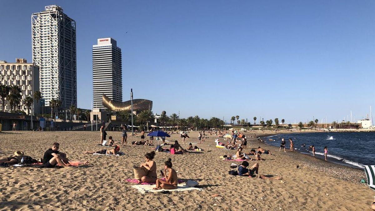 Bañistas toman el sol en la playa de Somorrostro