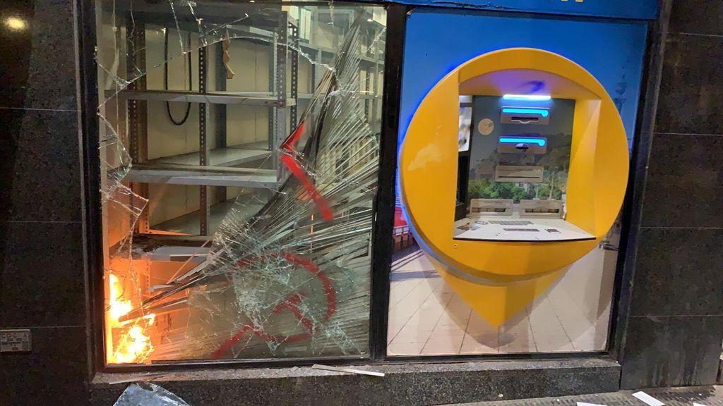 Sucursal bancaria en llamas destrozada por un grupo de manifestantes