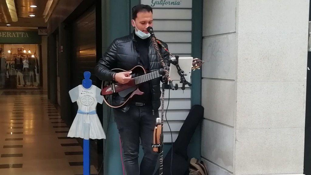 Cristian Navarro tocando su guitarra en la calle Príncipe de Vigo