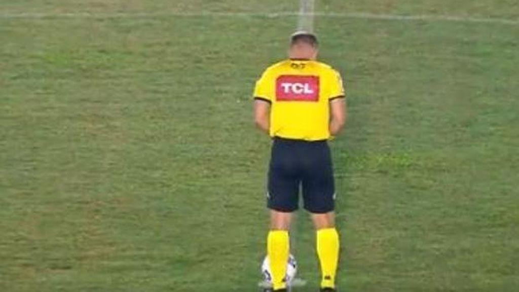 Un árbitro orina en el césped junto al balón antes del pitido inicial de un partido