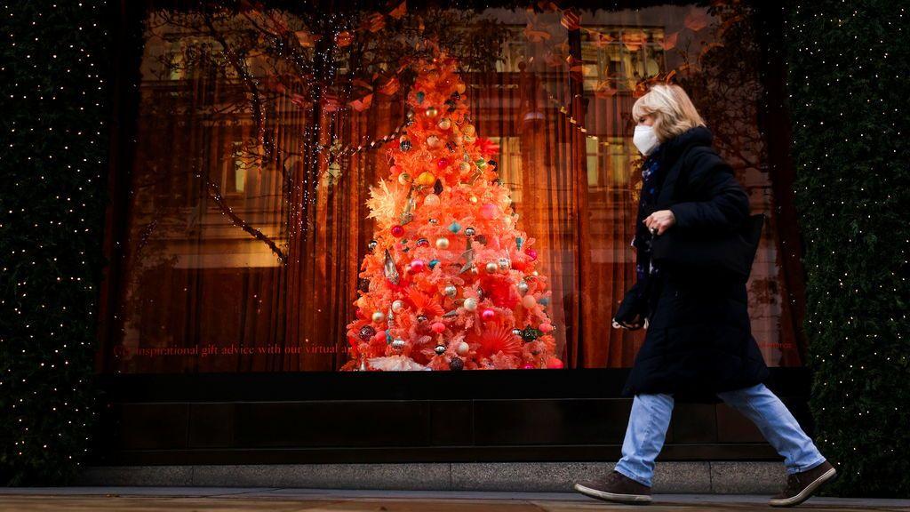 Una mujer con mascarilla pasea junto al árbol de Navidad de un establecimiento