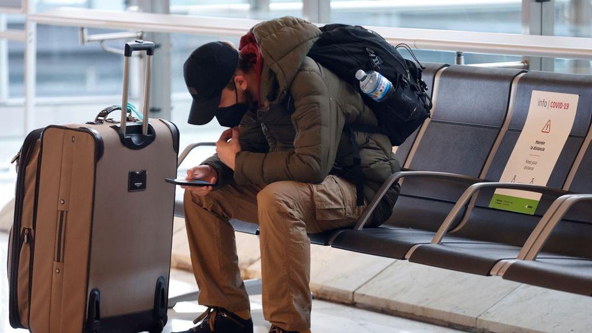 Un joven se sienta en un banco del aeropuerto de Madrid