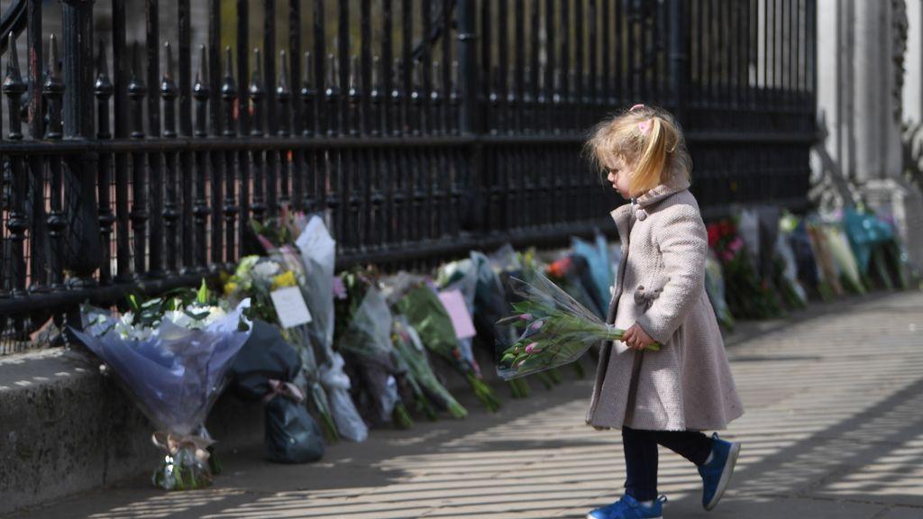 Una niña se dispone a colocar flores a la puertas del Palacio de Buckingham de Londres