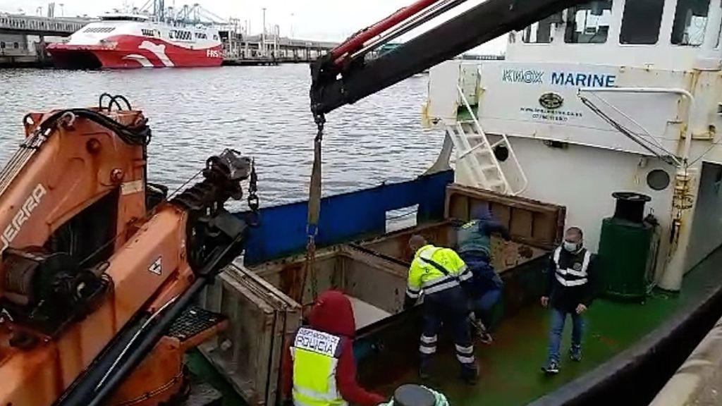 La grúa sacando sacos de hachís del remolcador