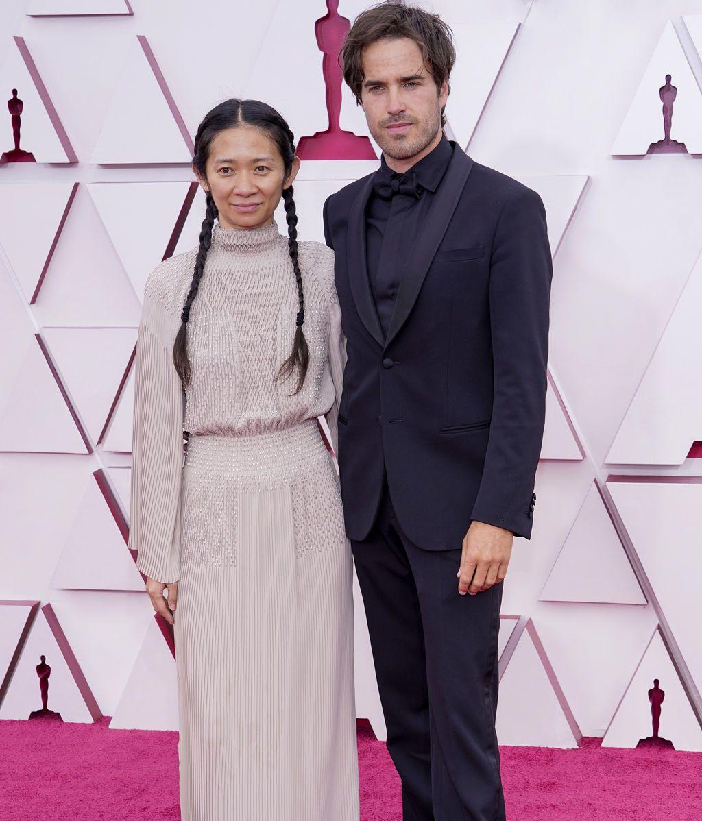 Chloe Zhao y Joshua James Richards desfilan en la alfombra roja de Union Station, la estación de autobuses de Los Ángeles, una de las sedes donde tiene lugar la gala de los Premios Oscars 2021