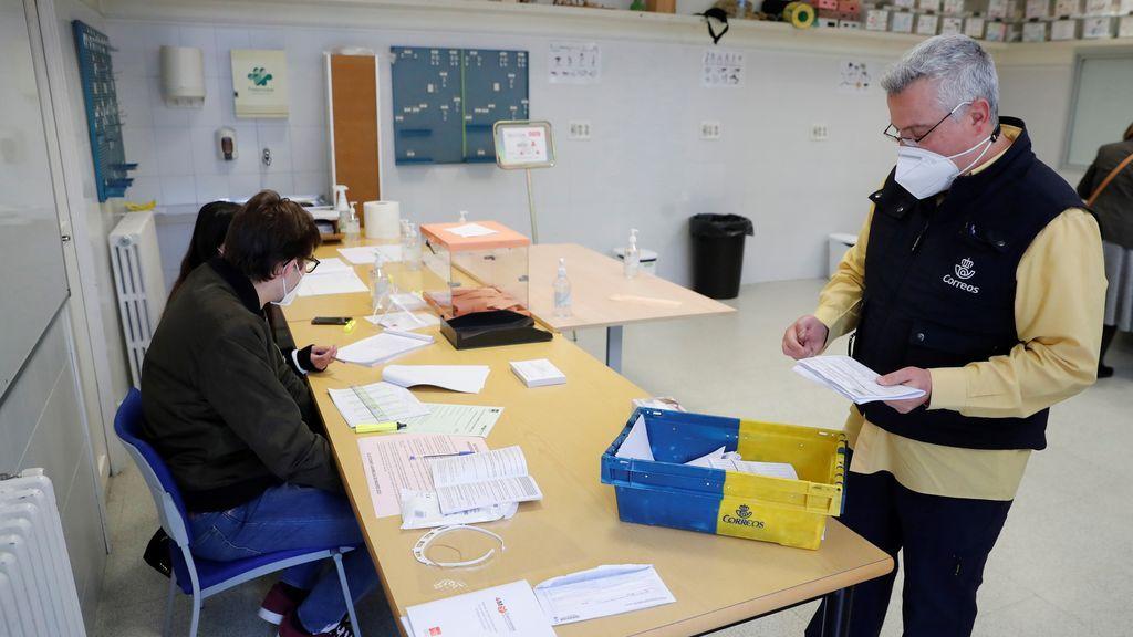 Trabajadores de Correos entregan el voto por correo en el colegio electoral de Nuestra Señora de Loreto