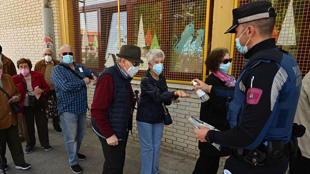 Un policía ofrece gel hidroalcohólico a votantes que esperan su turno
