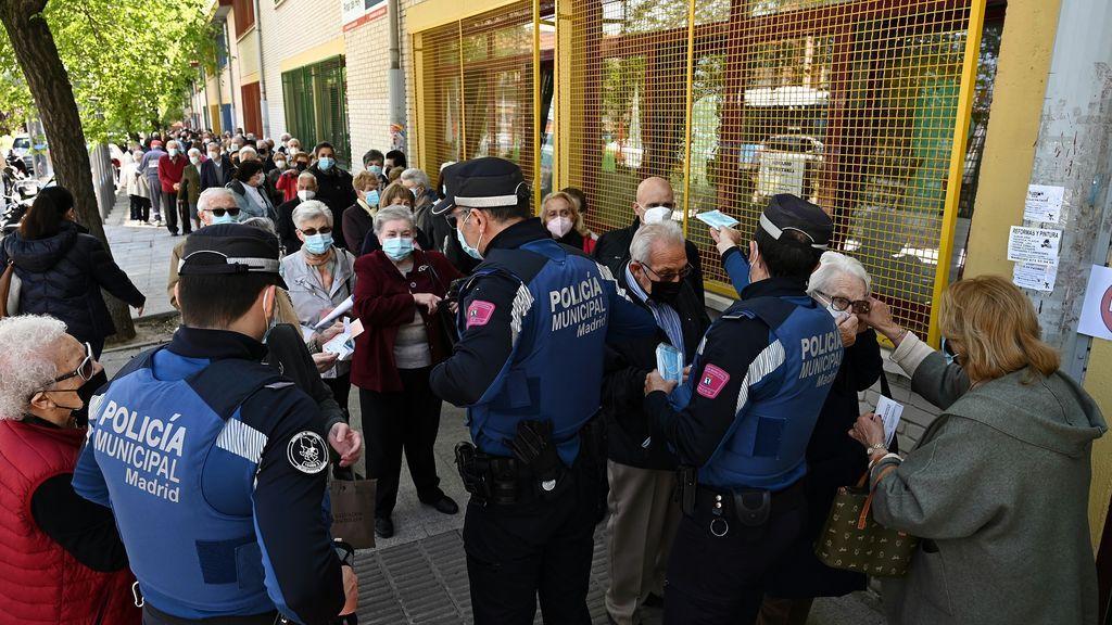 Policías reparten mascarillas entre votantes que esperan su turno para ejercer su derecho al voto