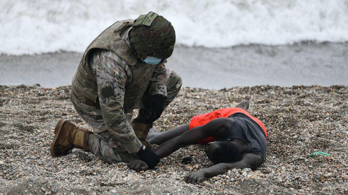Un militar del ejército español ayuda a una persona tumbada en la orilla tras alcanzar Ceuta desde Marruecos.