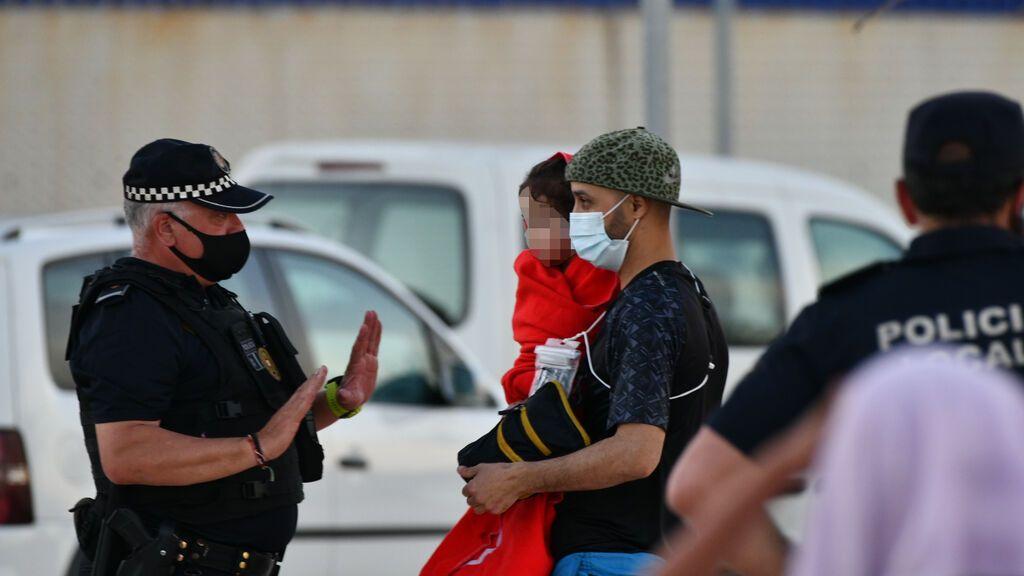 EuropaPress_3717565_policia_junto_hombre_migrante_coge_brazos_nina_playa_tarajal_17_mayo_2021