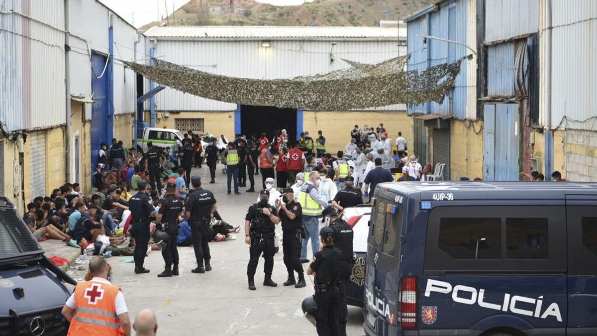 Profesionales sanitarios realizan pruebas PCR y atienden a varios jóvenes en la nave de primera acogida del polígono del Tarajal, en Ceuta.