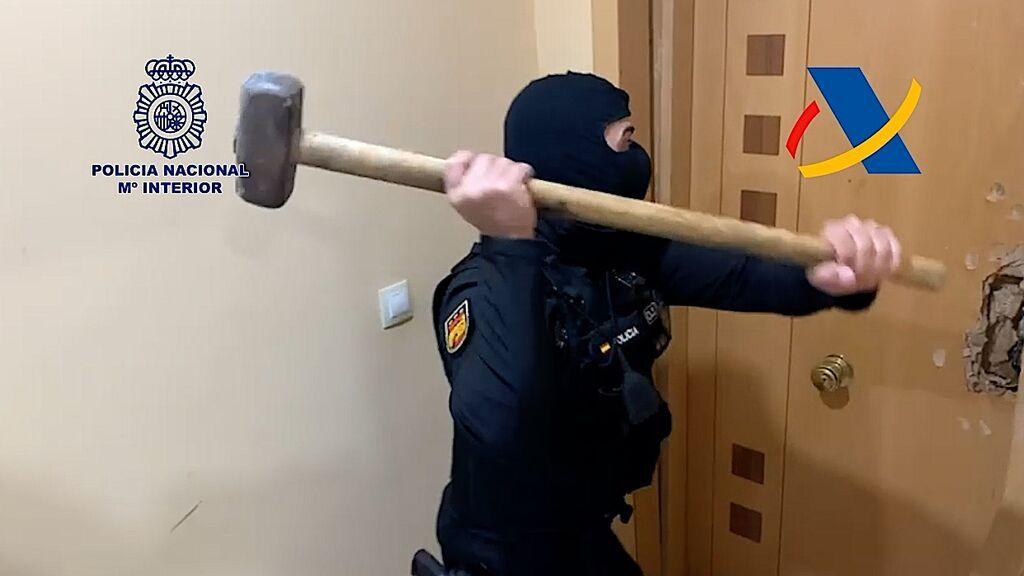 Un policía derriba una puerta en uno de los registros