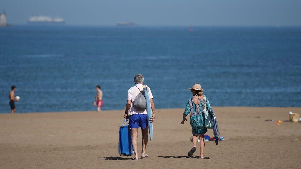 Dos personas pasean por la playa de Ereaga