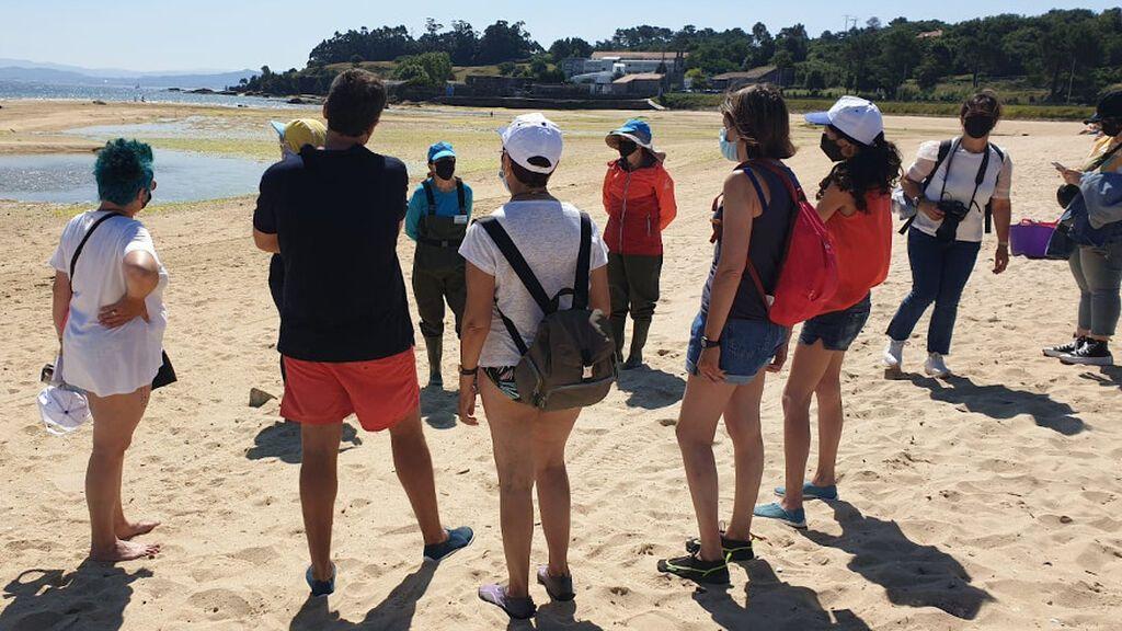 Turistas escuchan las explicaciones de las mariscadoras en la playa