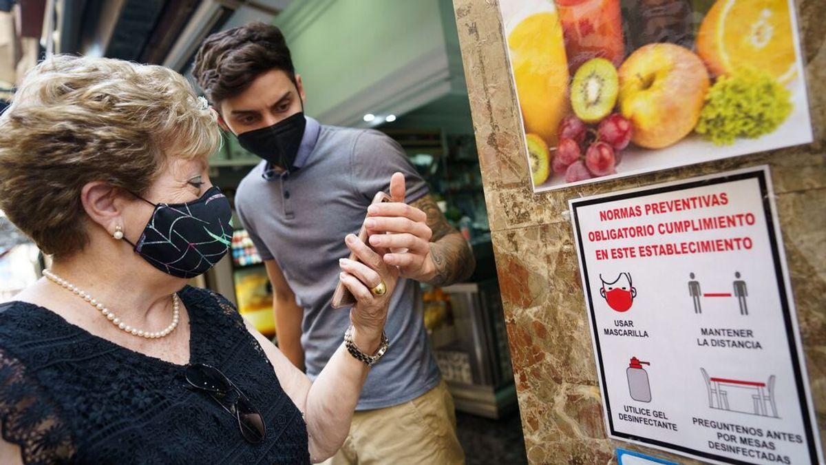 Un empleado de una cafetería en Canarias pide el certificado a una clienta
