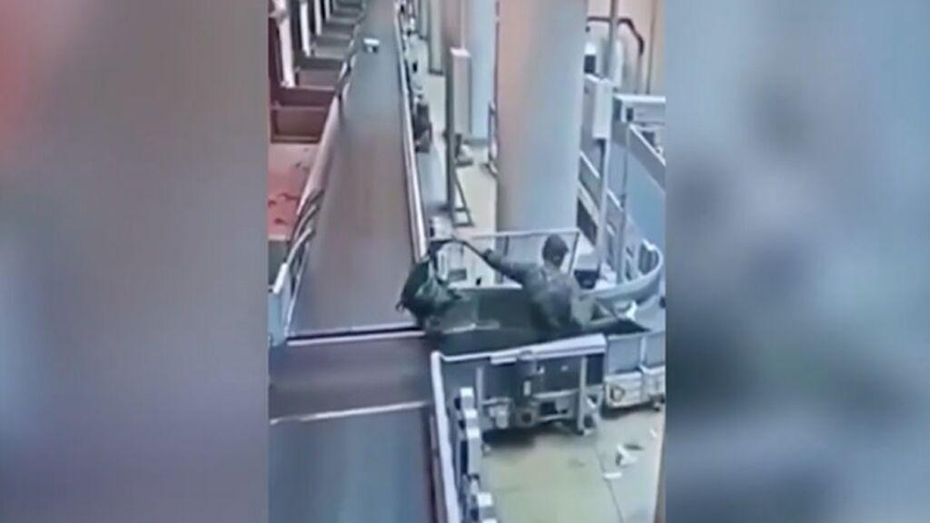 Un pasajero ebrio se cuela en la cinta transportadora del equipaje en un aeropuerto de Moscú, Rusia