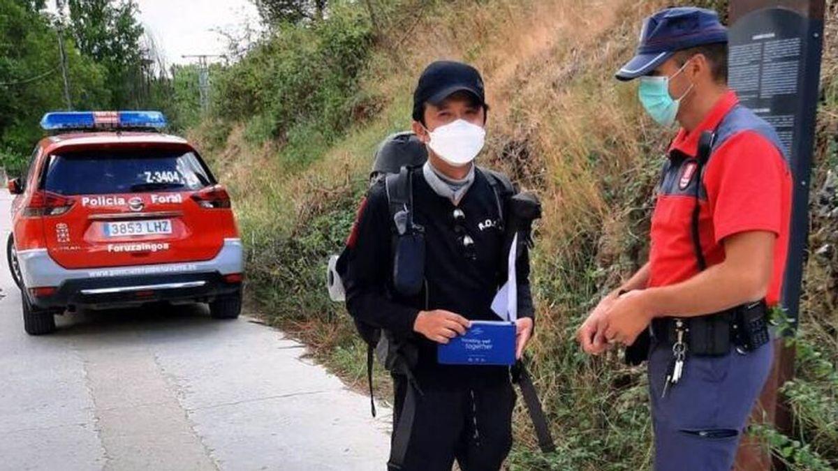 Un agente entrega la cartera al peregrino en Estella (Navarra)