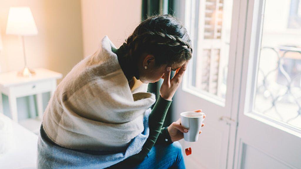 Imagen de archivo de una mujer con dolor de cabeza sosteniendo un vaso