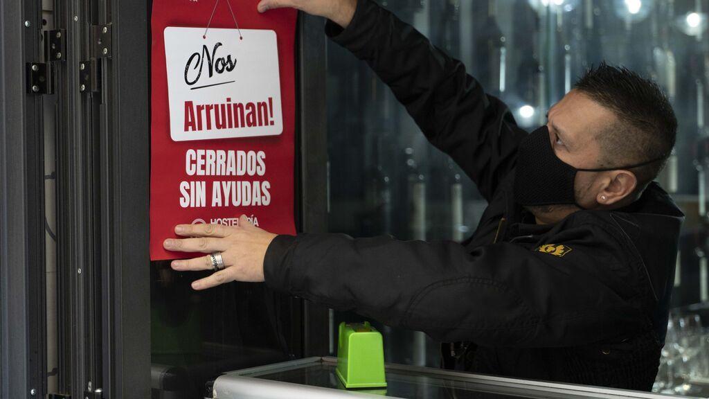 EuropaPress_3456098_trabajador_hosteleria_coloca_cartel_donde_lee_nos_arruinan_cerrados_ayudas