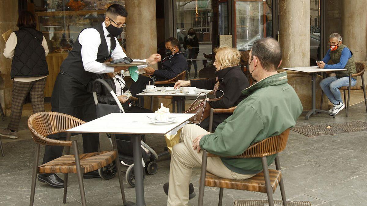 Un camarero atiende a varios clientes en la terraza de un bar en Palma