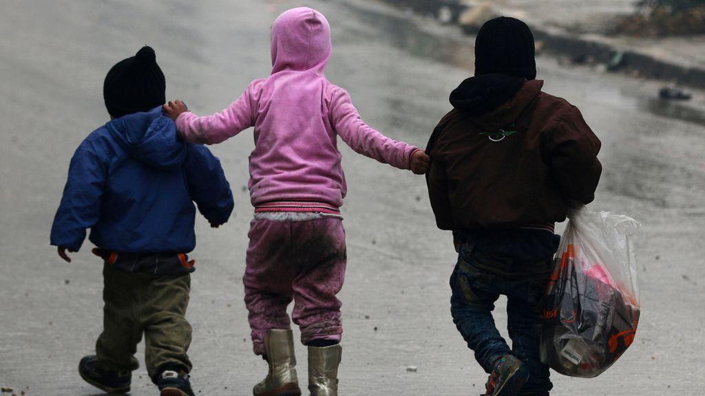 Tres niños caminan solos por las calles de Alepo