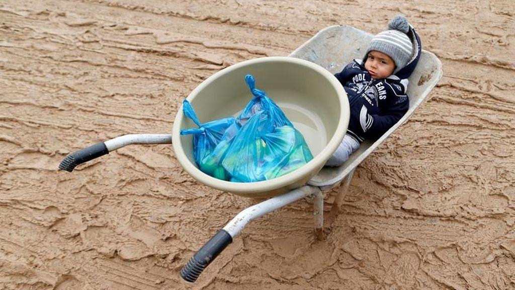 Un niño se sienta en una carretilla en el campo de Khazer
