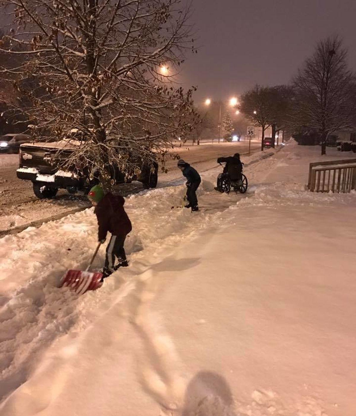 Sus hijos se bajan del coche para ayudar a un hombre en silla de ruedas a quitar la nieve