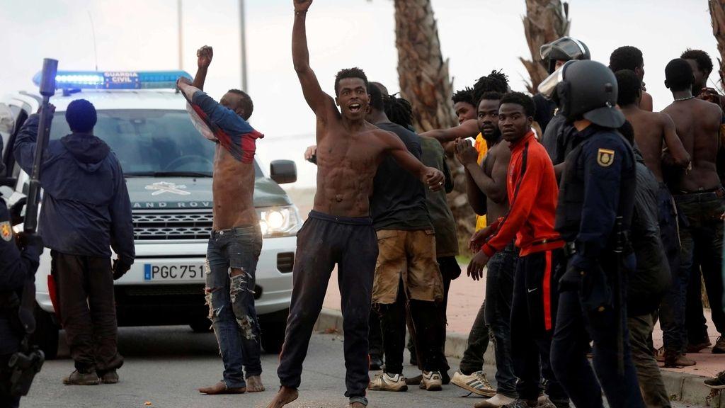 Inmigrantes que han saltado hoy la valla de Ceuta junto a miembros de la Policía Nacional