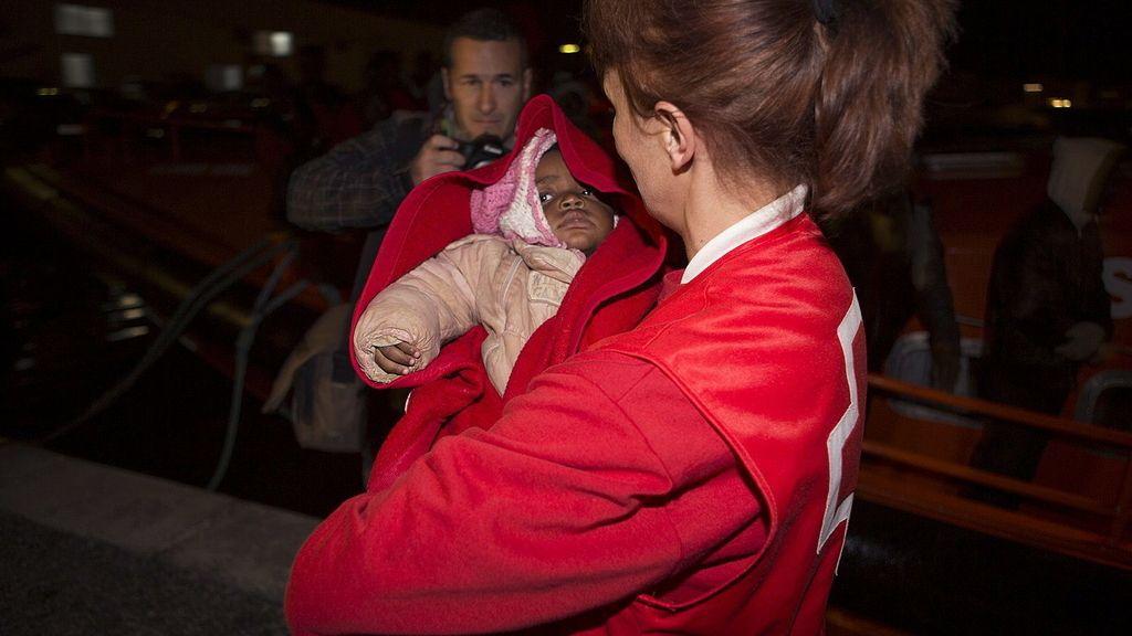 Una integrante de la cruz roja arropa al bebe que viajaba en una de las pateras rescatadas