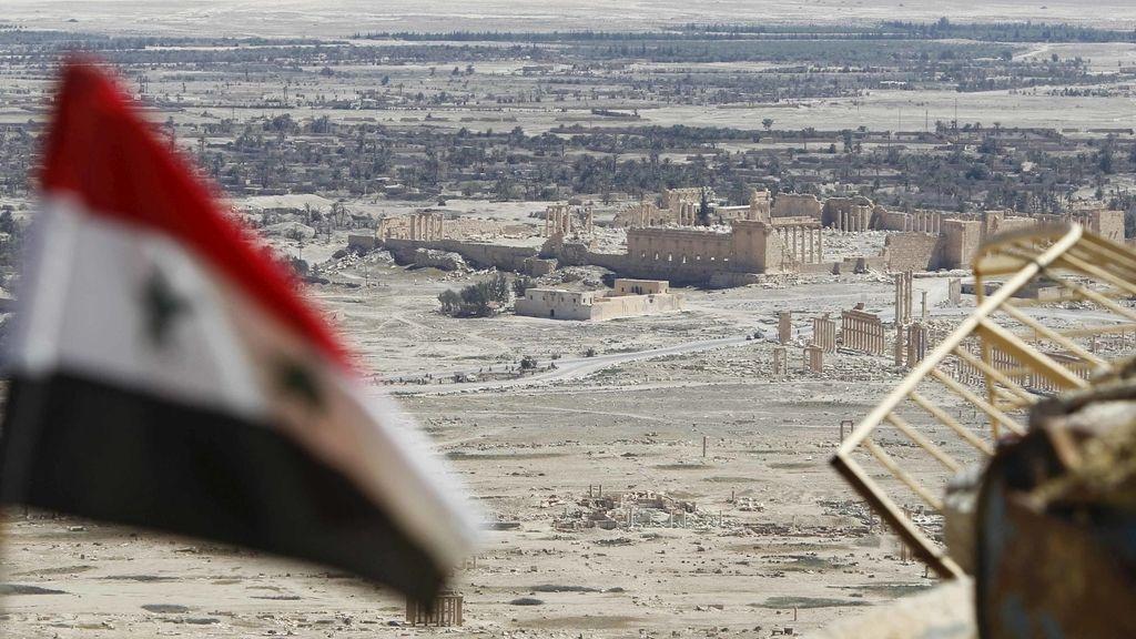 Una bandera nacional siria revolotea con las ruinas de la histórica ciudad de Palmira al fondo