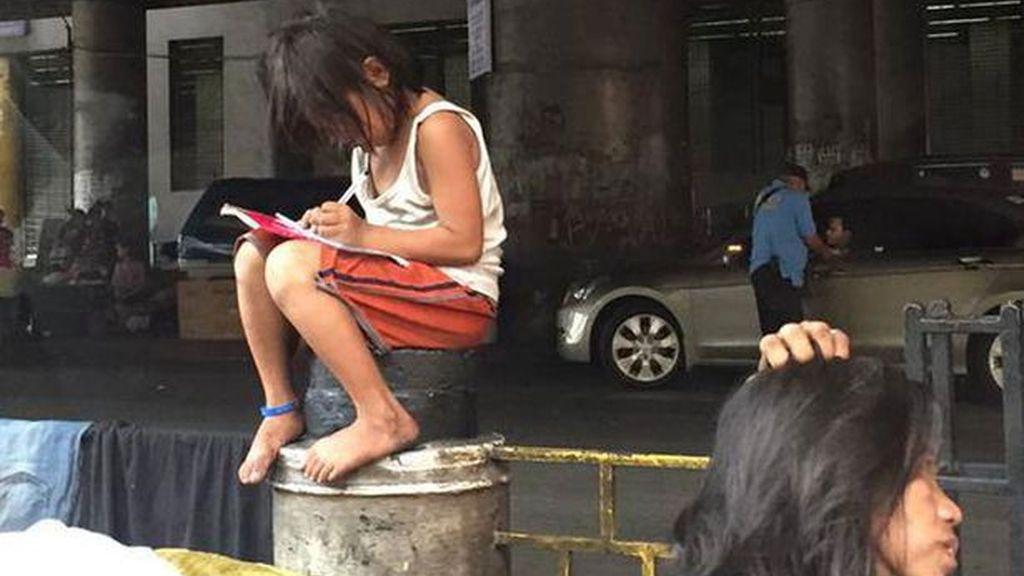La imagen de una niña filipina haciendo los deberes en la calle conmociona la Red