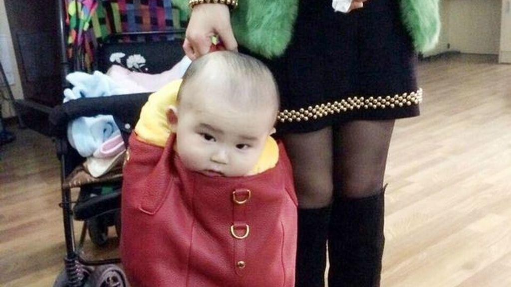 Un bebé pasea en el bolso de firma de su mamá