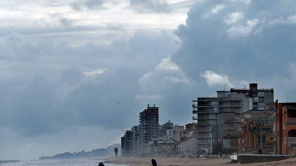 Un hombre pasea por la solitaria playa de El Perellonet, Valencia.