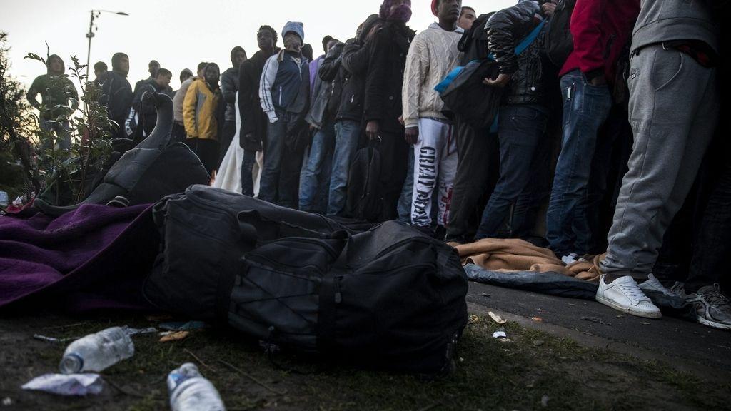 Migrantes hacen cola para subir a un autobús cerca de Calais