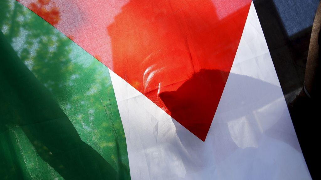 Un refugiado palestino sujeta la bandera