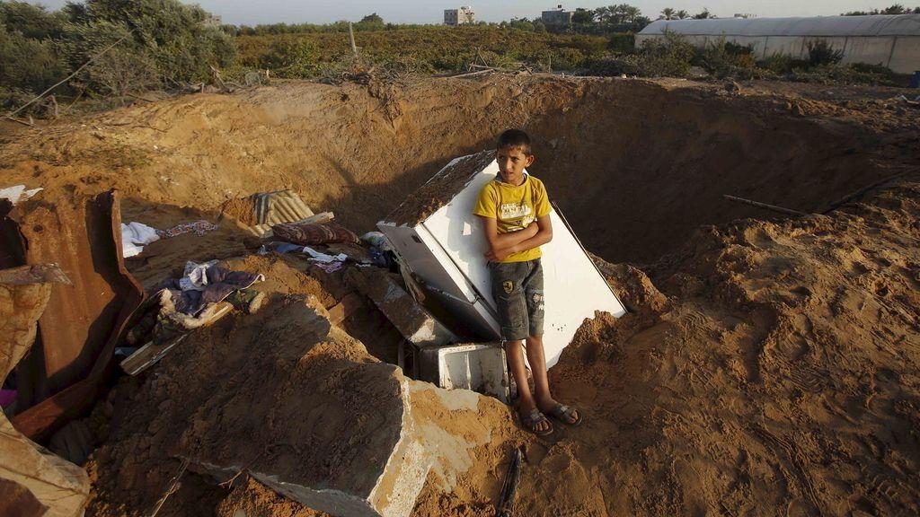 Niño palestino junto a los restos que ha dejado el ataque israelí