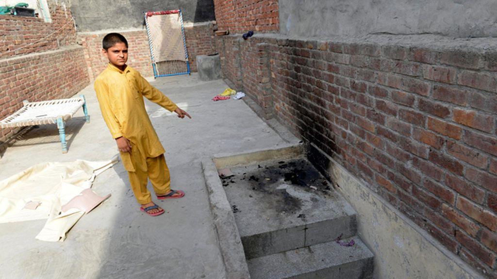 Un niño muestra el lugar donde una adolescente ha sido quemada viva por su madre en Lahore, Pakistán