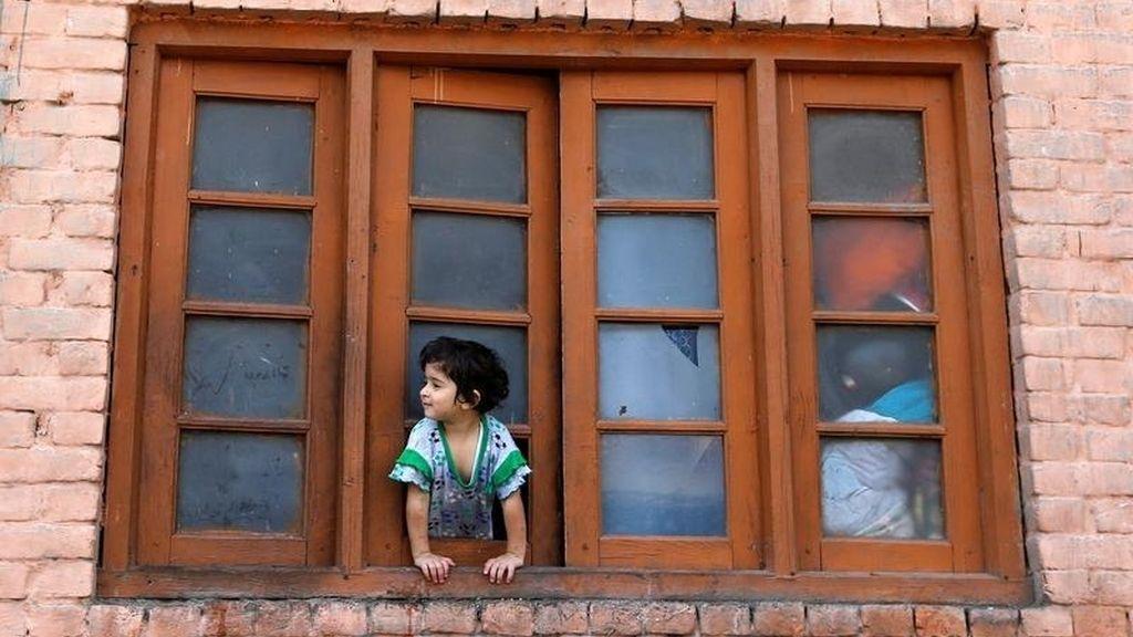 Una niña asoma la cabeza por la ventana de su casa durante el toque de queda en Srinagar