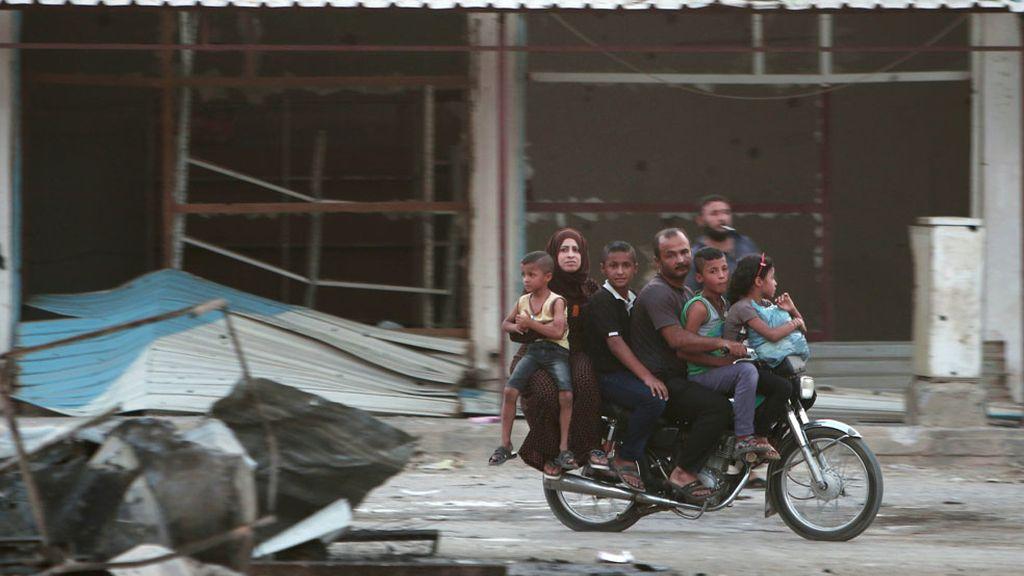 Miembros de una familia montan en una motocicleta en Siria