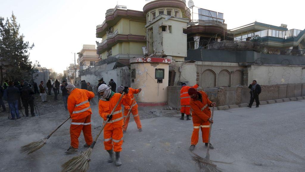 Trabajadores municipales afganos barren una carretera después del un ataque