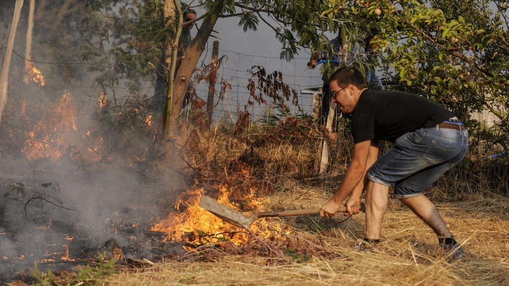Un vecino intenta apagar las llamas en la provincia de Ourense