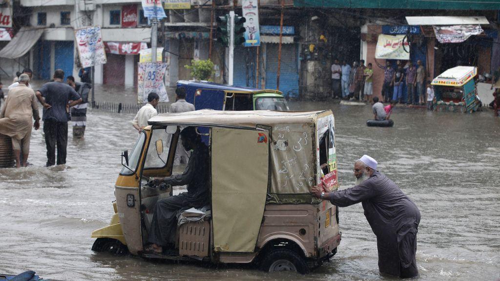 Un hombre empuja un auto rickshaw en medio del agua