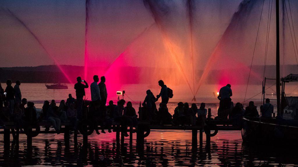 Visitantes miran la fuente iluminada en Steinhude, Alemania
