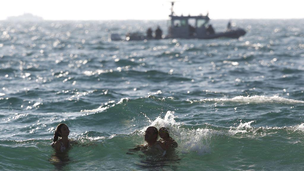 Israelíes se bañan en la playa frente a una patrulla israelí