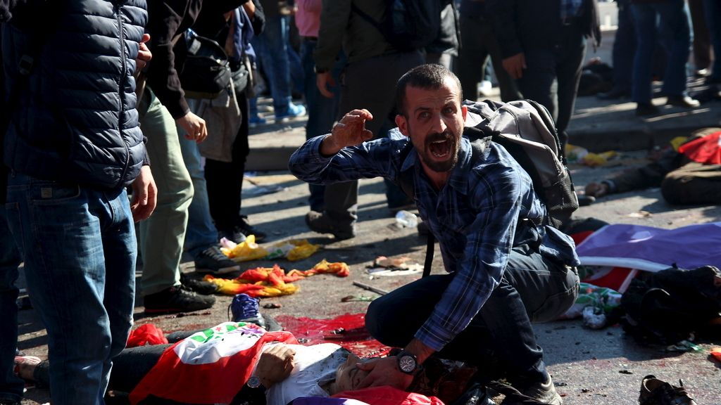 Un hombre junto a uno de los cientos de cadáveres de Ankara
