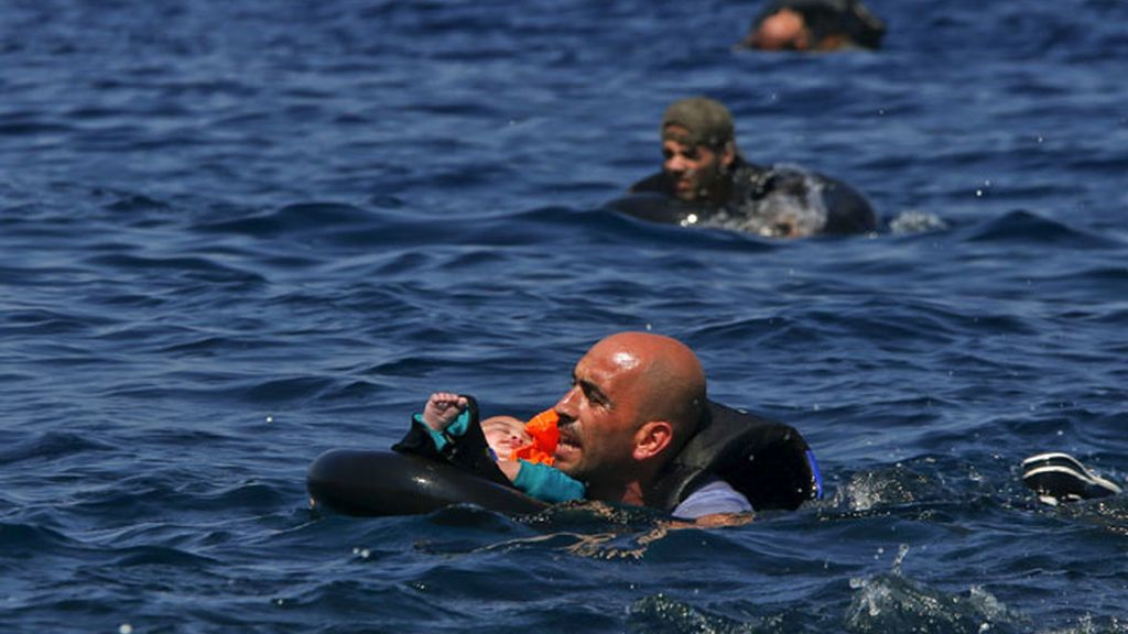 Llegada de refugiados a Lesbos. Un hombre sujeta a un bebé.