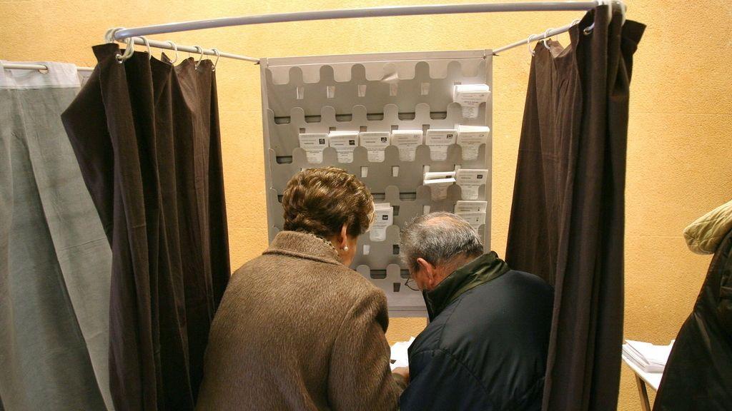 Dos personas preparan sus papeletas esta mañana en un colegio electoral en Tarragona
