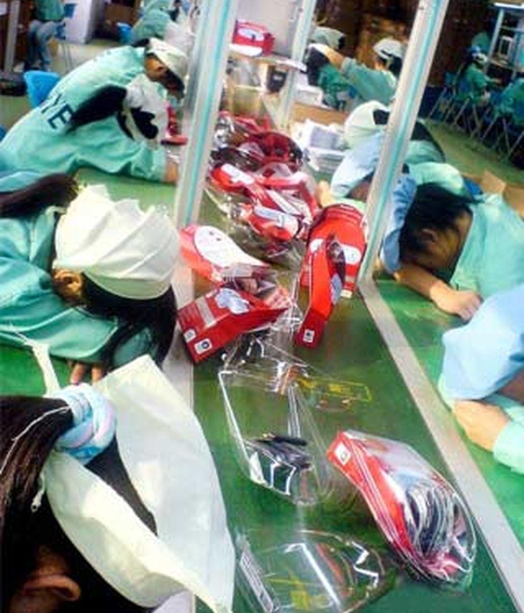Imagen conseguida por la NLC de trabajadores chinos dormidos sobre sus mesas de trabajo. Foto: The Daily Mail