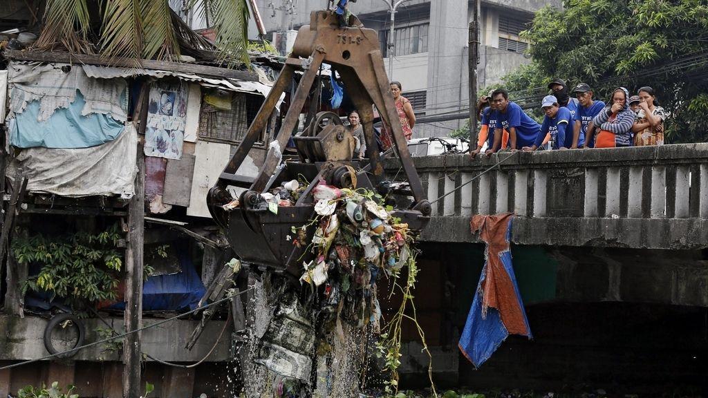 Trabajadores municipales retiran basura de un río en Manila (Filipinas)